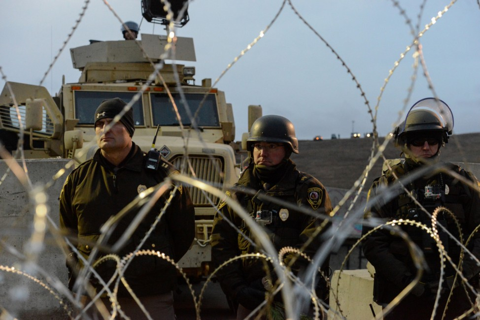 Police stand guard during a prayer ceremony on Backwater Bridge during a protest against plans to pass the Dakota Access pipeline near the Standing Rock Indian Reservation, near Cannon Ball, North Dakota