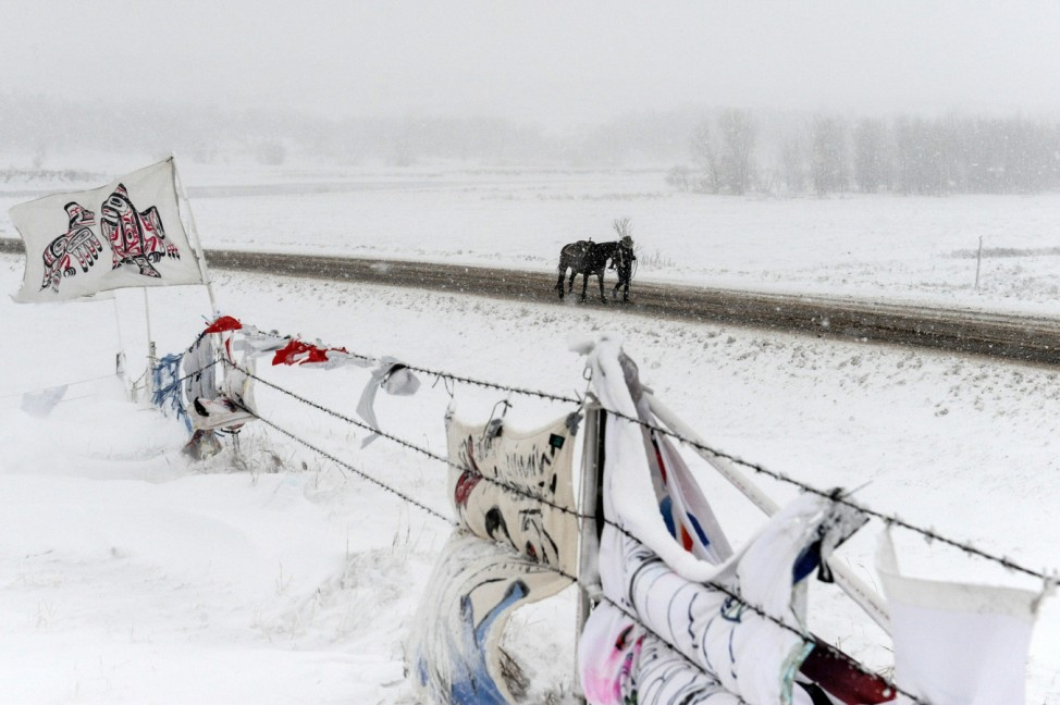 A person walks a horse past the Oceti Sakowin camp in a snow storm during a protest against plans to pass the Dakota Access pipeline near the Standing Rock Indian Reservation, near Cannon Ball, North Dakota, U.S.