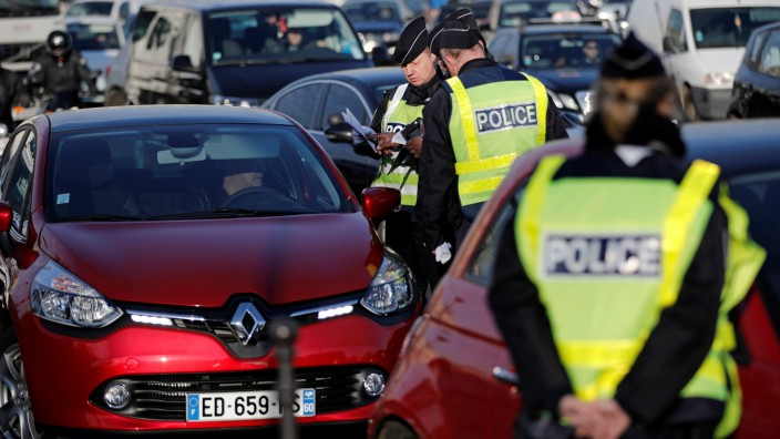 French policemen check automobile registration plates as authorities imposed alternate vehicle circulation days to reduce car traffic and pollution in Paris