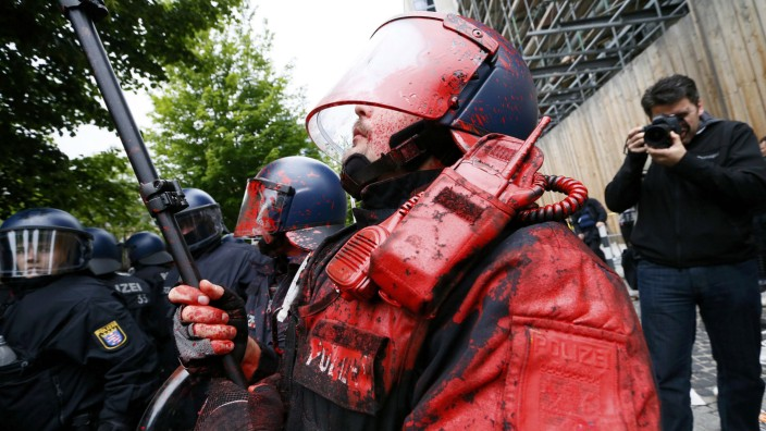 Photographer takes pictures of a German riot policeman, hit by a paint bomb, during an anti-capitalism 'Blockupy' demonstration in Frankfurt