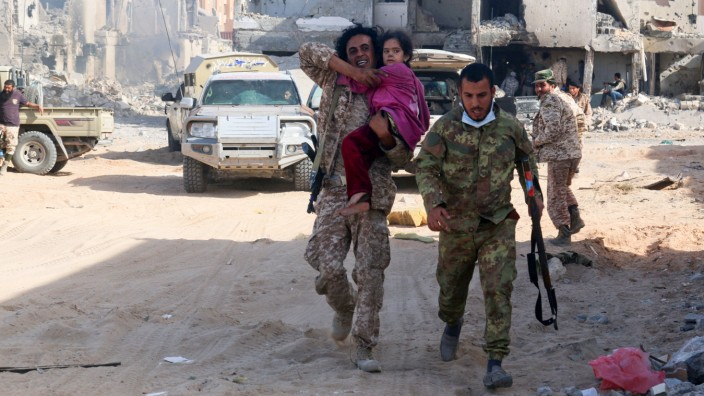 Fighter of Libyan forces allied with the U.N.-backed government carries a girl after she was released  from Islamic State-held ground as forces clear Ghiza Bahriya, the final district of the group's former stronghold of Sirte