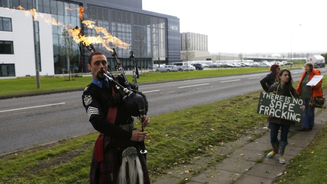 A man plays flaming bag pipes as opponents of fracking protest outside the offices of Ineos after they received the first shipment of shale gas to be delivered to the Britain at their Grangemouth  terminal in Scotland
