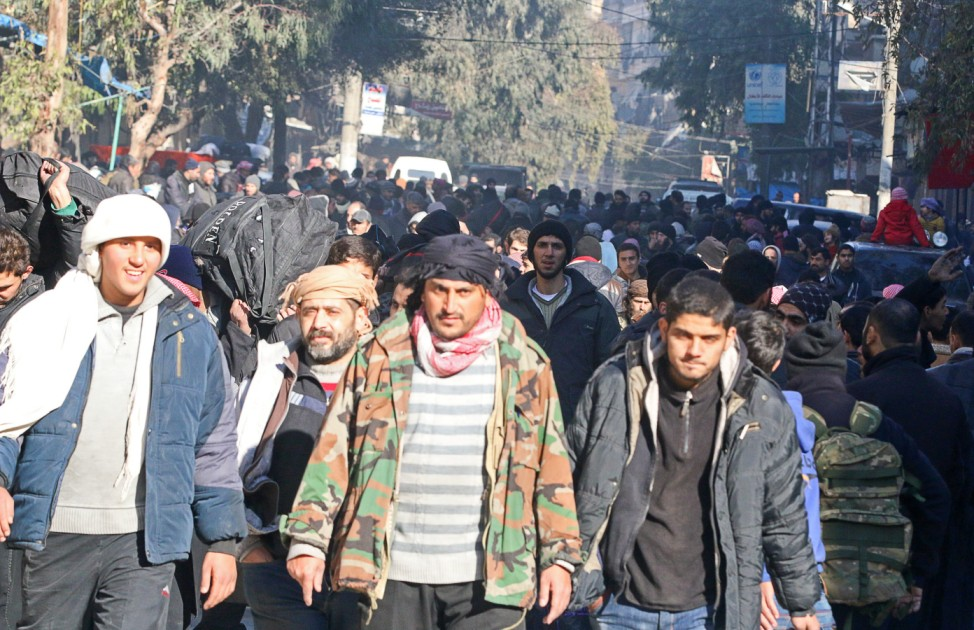 People gather to be evacuated from a rebel-held sector of eastern Aleppo
