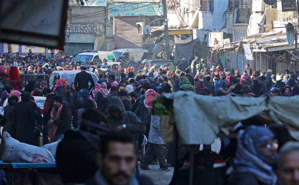 People gather to be evacuated from al-Sukkari rebel-held sector of eastern Aleppo