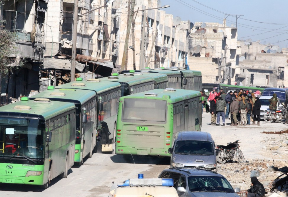 People get on buses to be evacuated from al-Sukkari rebel-held sector of eastern Aleppo