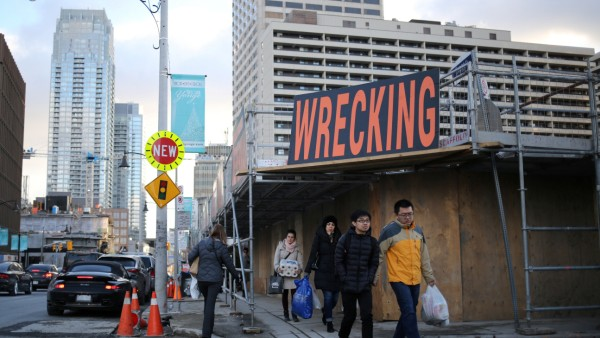 Shoppers pass the construction site of a condominium tower where a row of shops and restaurants had once stood in Toronto