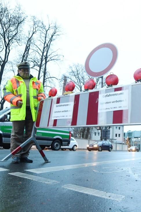 Polizisten errichten errichten am ersten Weihnachtsfeiertag in Augsburgeine Straßensperre. Für die Entschärfung einer Fliegerbombe sind etwa 4000 Einsatzkräfte im Dienst.