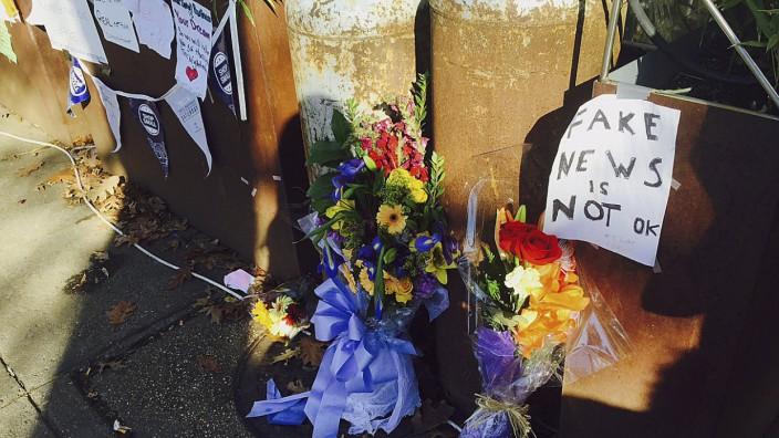 Fake News: Wegen gefälschter Meldungen über einen angeblichen Kinderpornoring stürmte ein bewaffneter Mann eine Pizzeria. Vor dem Laden haben Passanten Botschaften und Blumen hinterlassen.