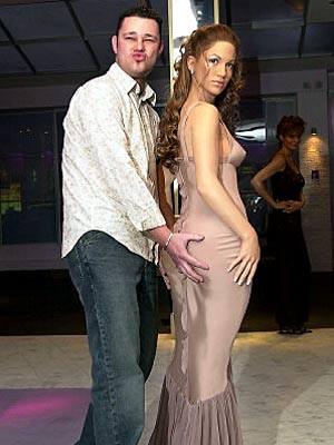 Angestellter von Madame Tussauds mit Wachsfigur von Jennifer Lopez bei Madame Tussaud's in London