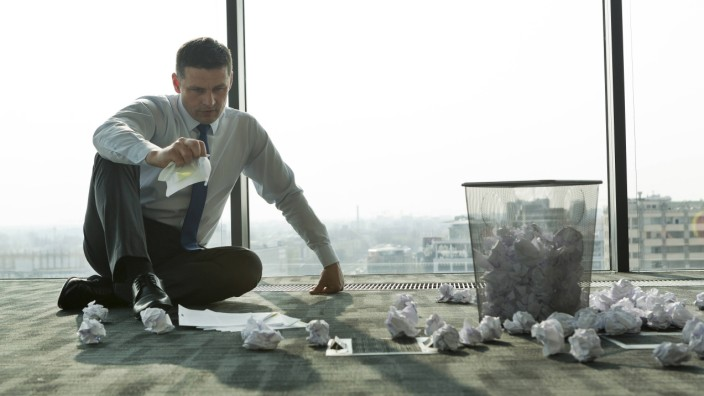 Businessman sitting on office floor surrounded by crumpled paper model released property released PU