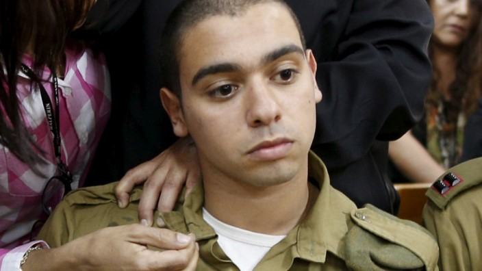 The father of an Israeli soldier who is charged with manslaughter prays behind him in a military court during a remand hearing in Kiryat Malachi