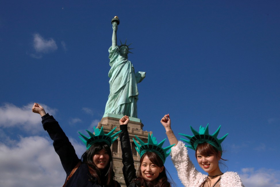 FILE PHOTO: Japanese tourists pose in front of The Statue of Liberty on the 130th anniversary of the dedication in New York Harbor