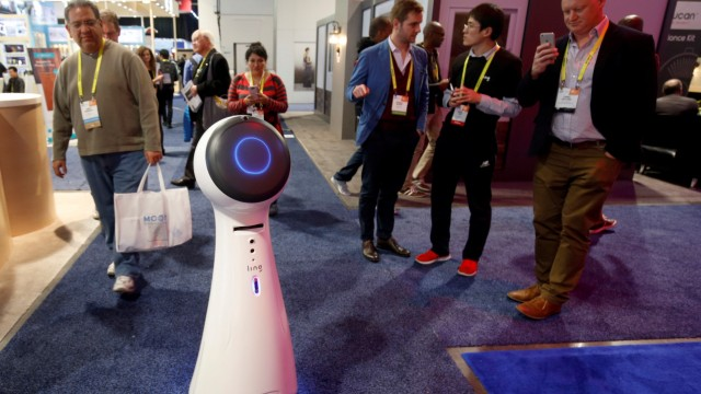 Wavebot, a service robot by Ling, travels down an aisle on the trade show floor during the 2017 CES in Las Vegas