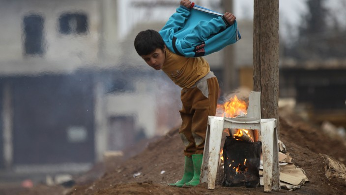A boy warms himself around a fire in the northern Syrian rebel-held town of al-Rai
