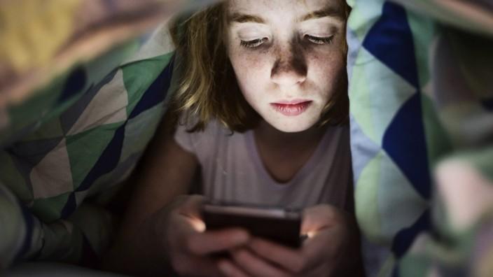 Ein Mädchen spielt unter der Bettdecke mit ihrem Smartphone