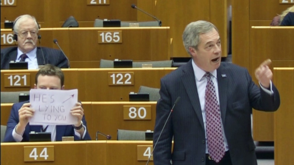 Labour Member of the European Parliament Seb Dance holding a sign that reads 'He's lying to you' behind former UKIP leader and MEP Nigel Farage, who is addressing the European Parliament in Brussels, in this still image taken from video