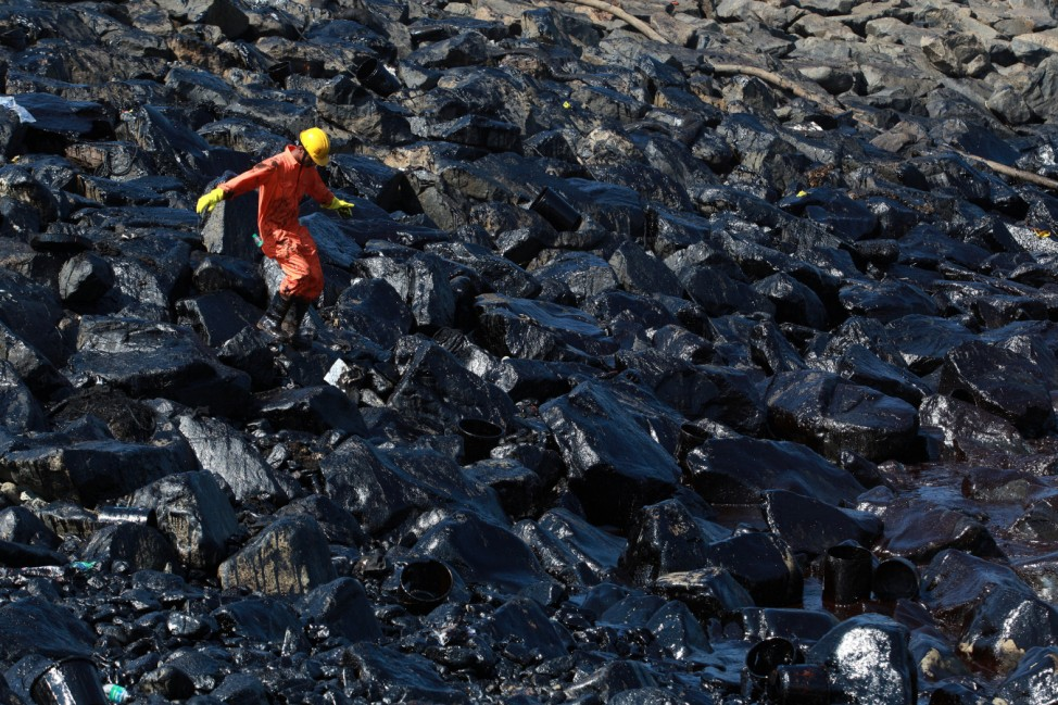 An emergency worker walks amidst oil deposits as he cleans oil from the shoreline of Ennore Port following a collision between two oil tankers, in Chennai