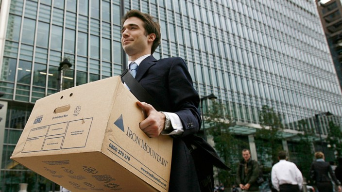 File photograph shows a worker carrying a box out of the U.S. investment bank Lehman Brothers in London