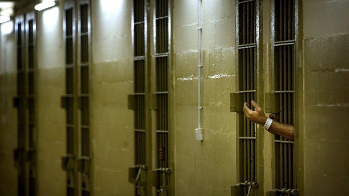File photo of an Iraqi detainee gesturing toward U.S. soldiers through bars of his cell at Abu Ghraib prison outside Baghdad