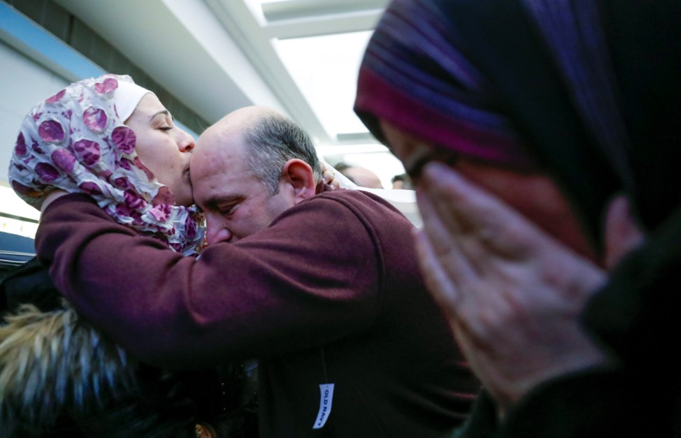 Syrian refugee Baraa Haj Khalaf kisses her father Khaled as her mother Fattoum cries after arriving at O'Hare International Airport in Chicago
