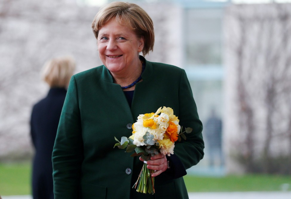 German Chancellor Merkel smiles after receiving flowers from Slovenian President Borut Pahor at the Chancellery in Berlin
