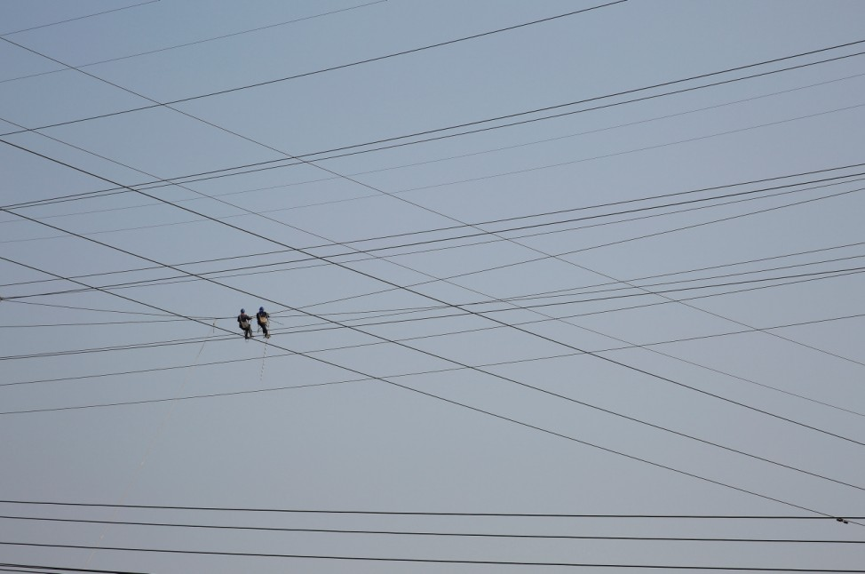 Workers work on high voltage power lines in Tongling