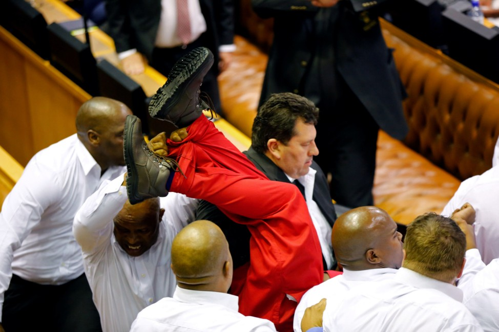 Security officials remove members of the Economic Freedom Fighters during President Zuma's State of the Nation Address in Cape Town