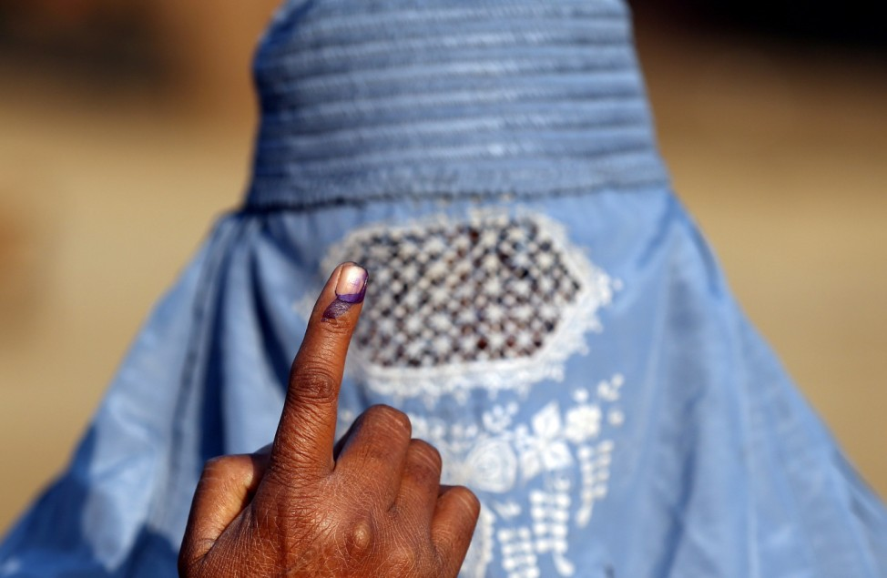 A woman shows her ink marked finger after voting during the state assembly election, in the village of Kairana, in the state of Uttar Pradesh