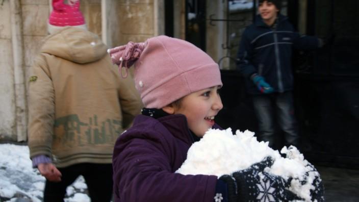 Mein Leben in Deutschland: Syrische Kinder spielen mit Schnee in Damaskus (Archivbild).
