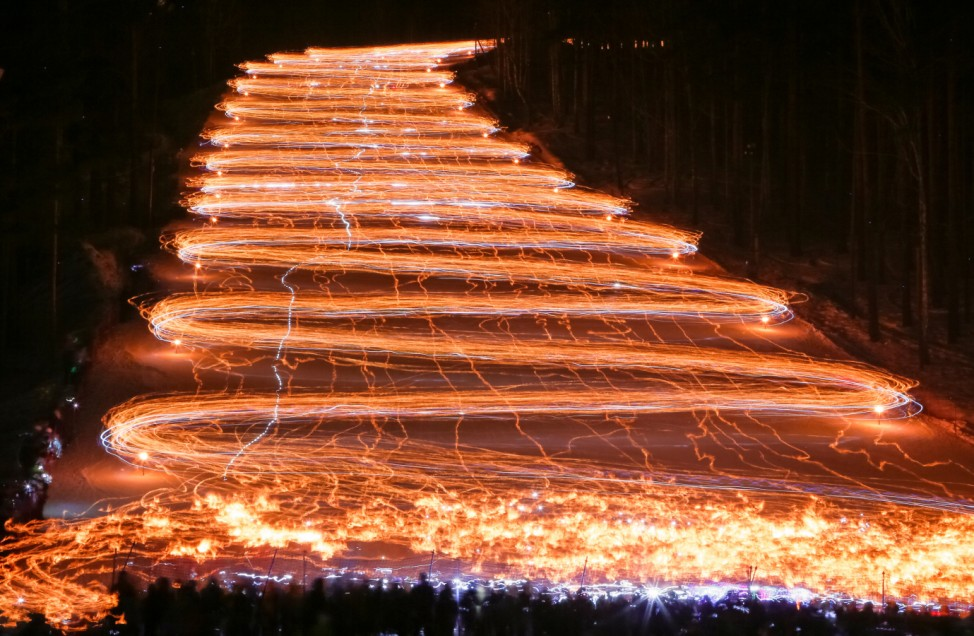 Hundreds of skiers and snowboarders descend from a slope while holding lit torches and flashlights in the Siberian town of Zheleznogorsk, northeast of Krasnoyarsk, Russia