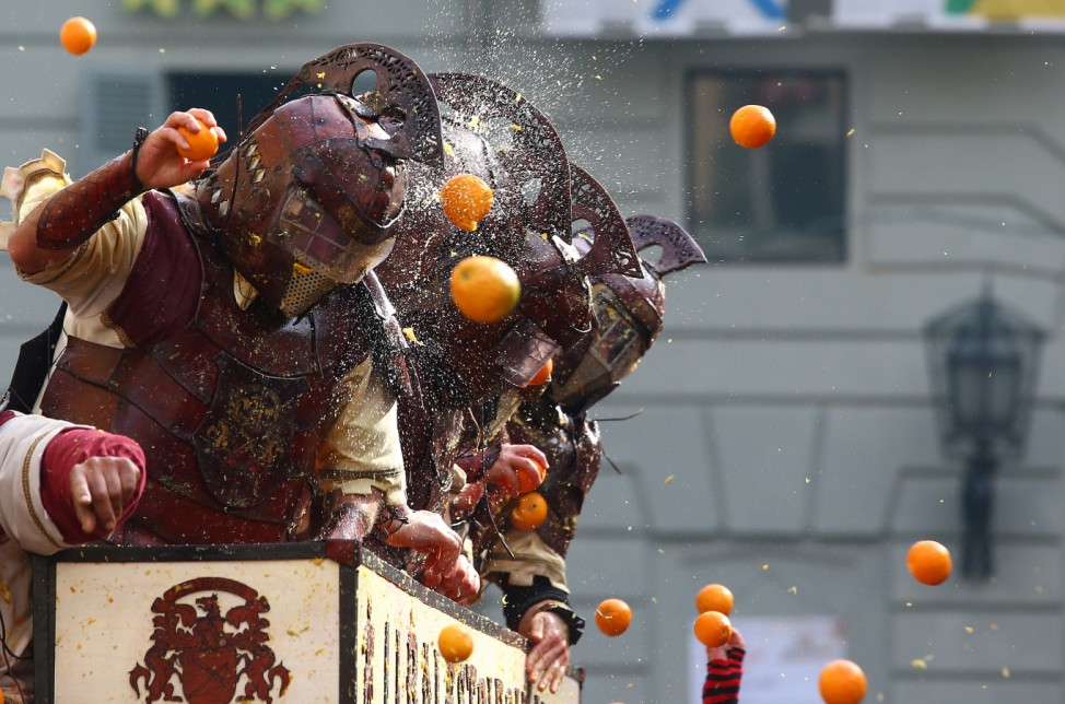 Members of a rival team are hit by oranges during an annual carnival orange battle in the northern Italian town of Ivrea
