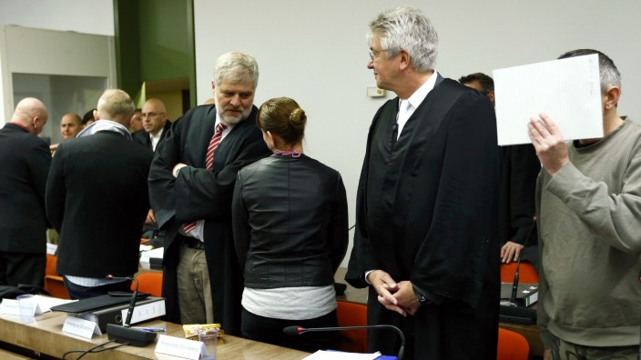 Defendants of far-right 'Oldschool Society' organisation stands between lawyers in courtroom in Munich