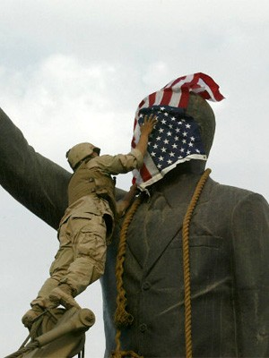US-Soldat verhüllt eine Statue von Saddam Hussein mit der US-Flagge