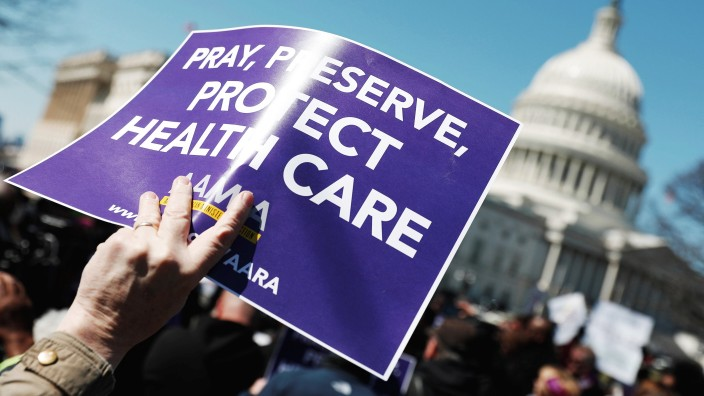 Demonstrators hold signs during a protest against the repeal of the Affordable Care Act outside the Capitol Building in Washington