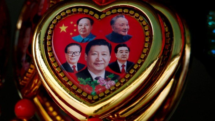 A picture shows a souvenir featuring portraits of former Chinese leaders Mao Zedong, Deng Xiaoping, Jiang Zemin, Hu Jintao and current President Xi Jinping on the second day of CPC in Beijing