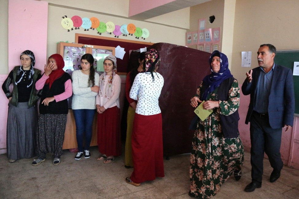 People wait to cast their votes at a polling station during a referendum in the Kurdish-dominated southeastern city of Diyarbakir
