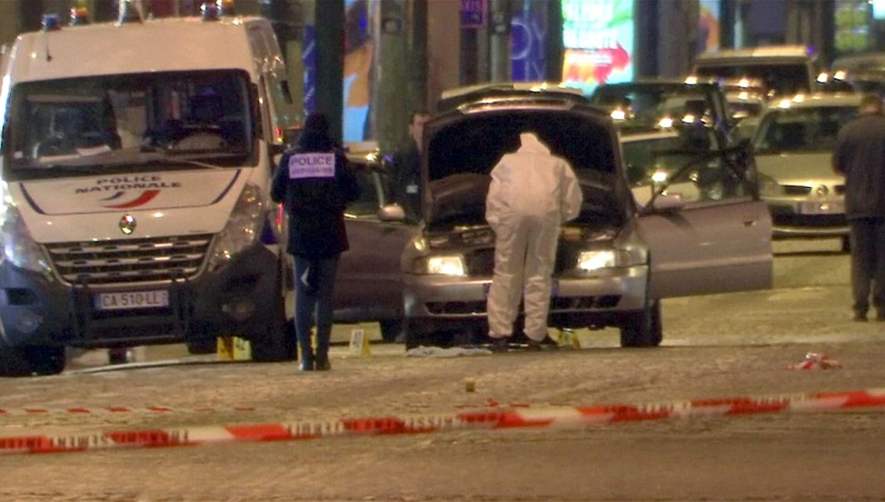 A still image from video footage shows Police investigators inspect the car used by the attacker on the Champs Elysees Avenue after two policemen were killed and another wounded in a shooting incident in Paris
