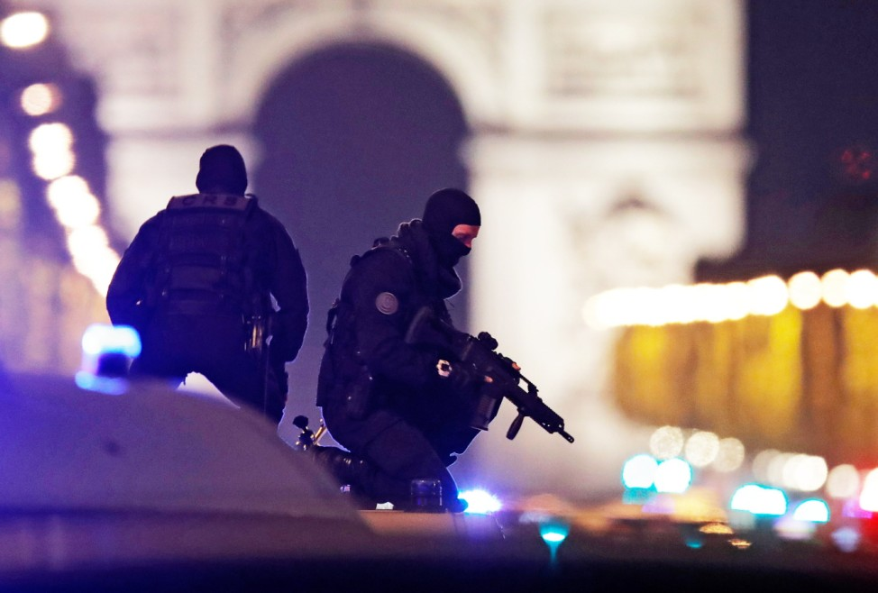 Masked police stand on top of their vehicle on the Champs Elysees Avenue after two policemen were killed and another wounded in a shooting incident in Paris
