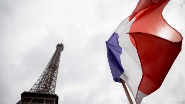 Die französische Trikolore weht vor dem Eifelturm in Paris im Wind.
