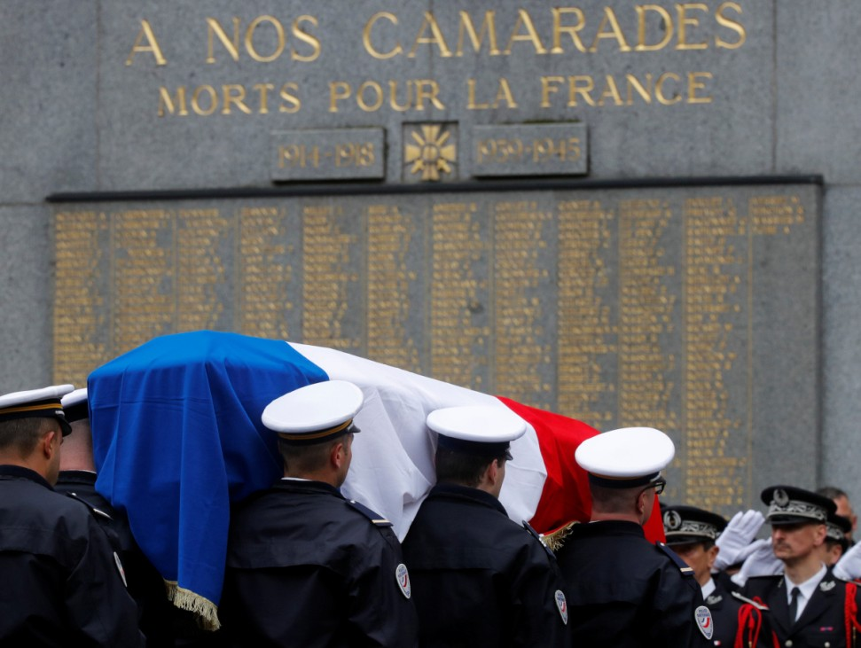 The flag-draped coffin of Xavier Jugele, the French police officer killed on the Champs Elysees avenue during a shooting incident, is carried by colleagues during a ceremony at the Police Prefecture in Paris