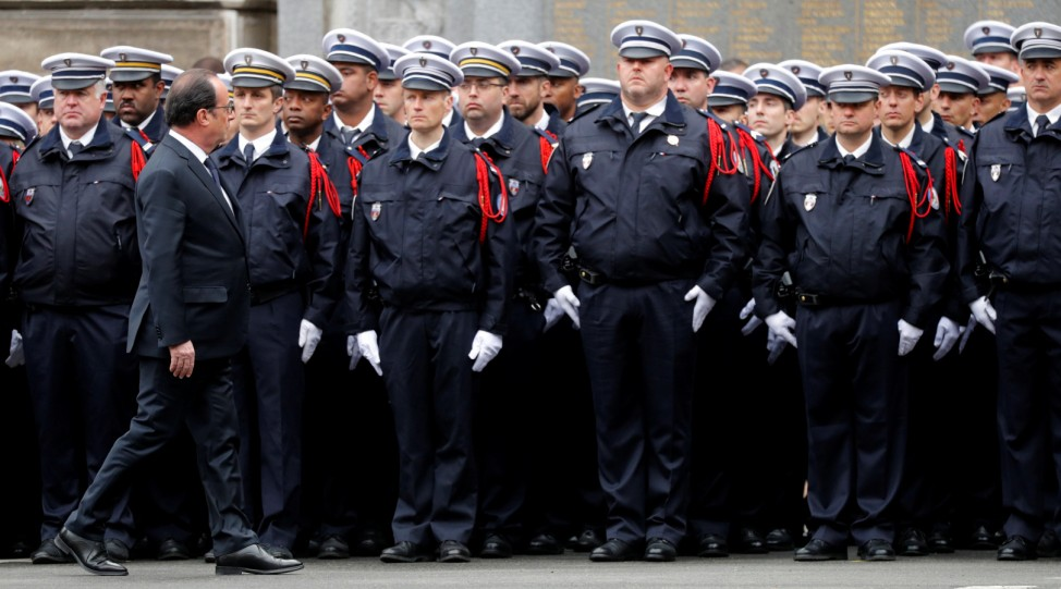 French President Francois Hollande reviews Police as he attends a ceremony at the Police Prefecture in Paris