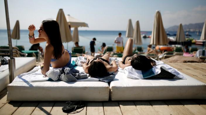 Tourists sunbathe on the beach in Eilat