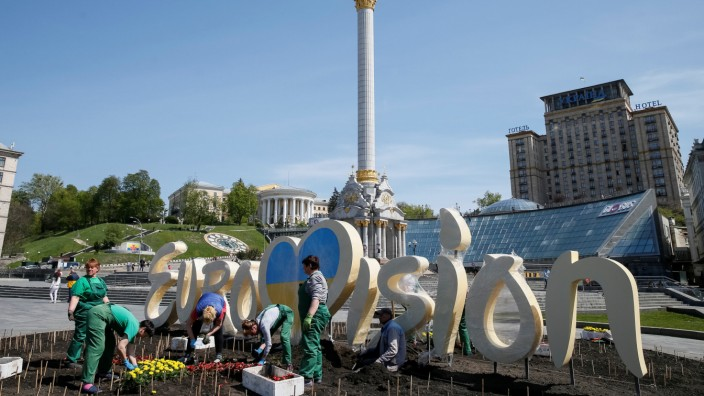 Communal workers tend a flowerbed, beside a logo of the Eurovision Song Contest 2017 in central Kiev