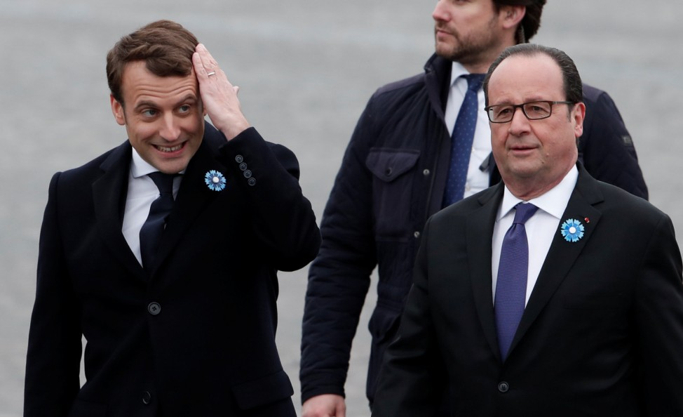 Outgoing French President Francois Hollande and President-elect Emmanuel Macron attend a ceremony to mark the end of World War II at the Tomb of the Unknown Soldier at the Arc de Triomphe in Paris