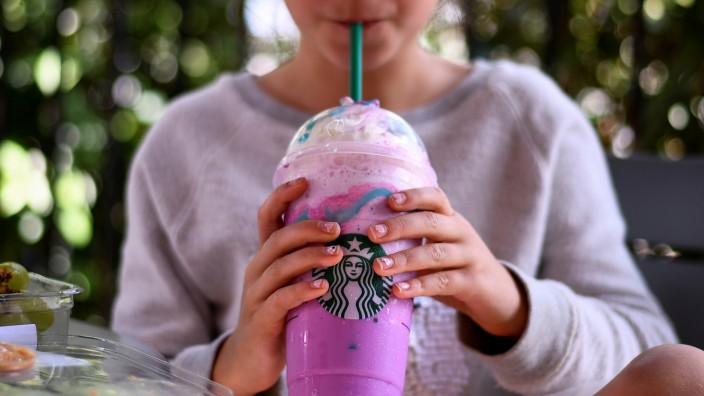 A girl sips on a Unicorn Frappuccino beverage at a Starbucks coffeehouse in Austin, Texas, U.S.