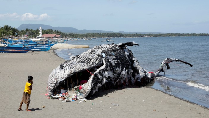 A boy looks at a whale shaped art installation that is made of plastic and trash made by environmental activist group Greenpeace Philippines in Cavite