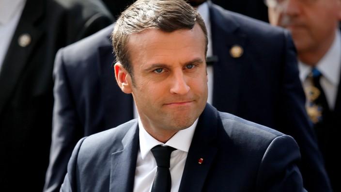 French President Emmanuel Macron buttons his vest outside the Hotel de Ville in Paris