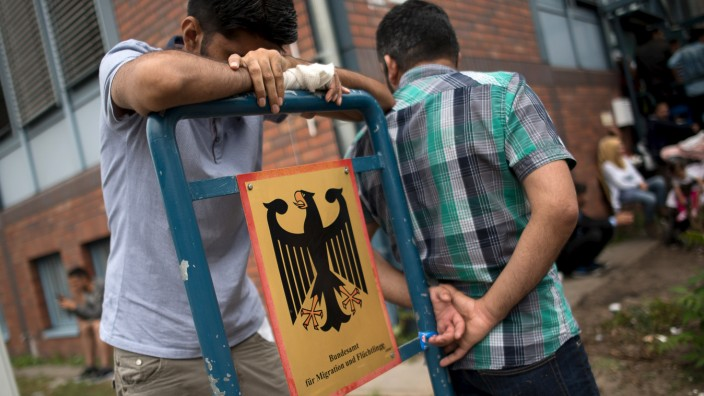 Asylum seekers wait in front of the Federal Office for Migration and Refugees (BAMF) at Berlin's Spandau district