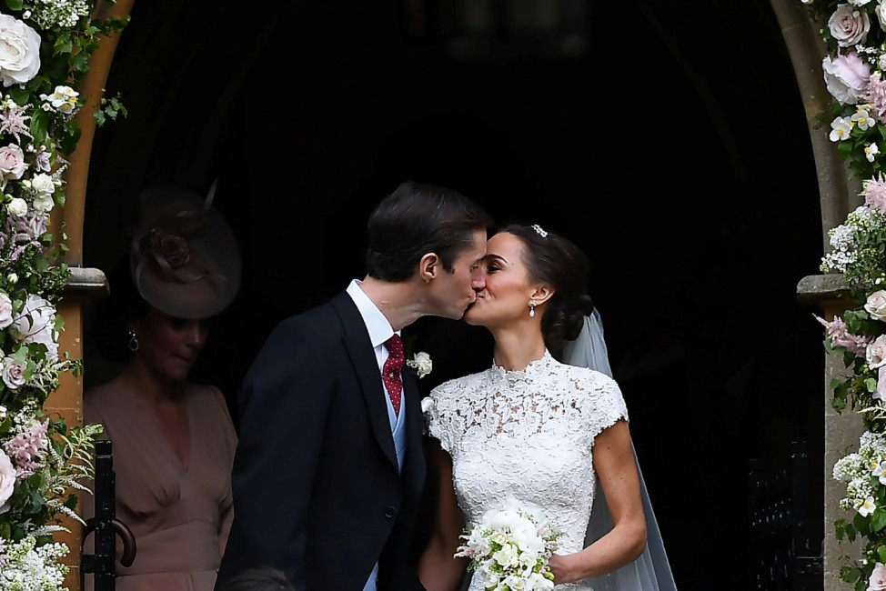Pippa Middleton kisses her new husband James Matthews, following their wedding ceremony at St Mark's Church in Englefield