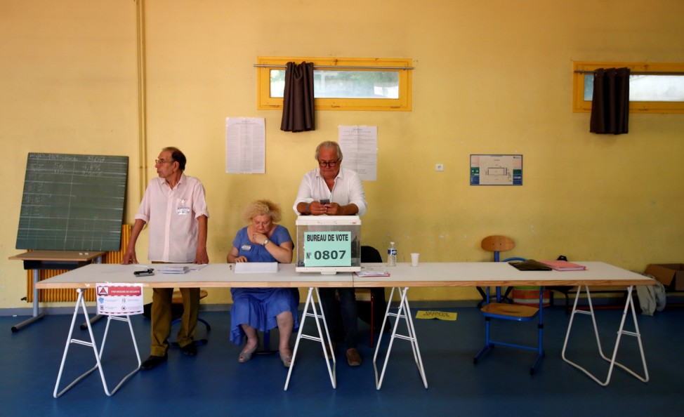 Electoral staff members wait voters at polling station in Marseille